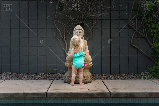 Toddler by Buddha statue at pool