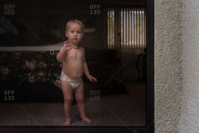 Toddler staring out glass door