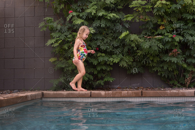 Girl walking by edge of pool