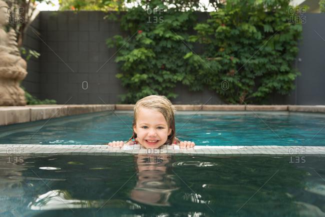 Girl smiling holding pool ledge
