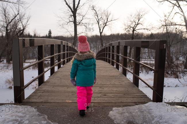 Girl crossing footbridge in winter