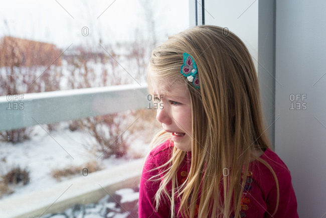 Girl crying looking out window