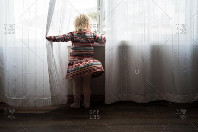 Girl peeking through curtains out window