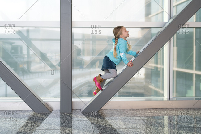Girl climbing beam in modern building