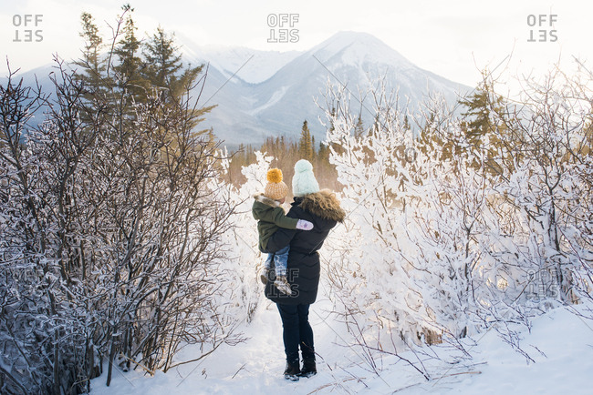 Mom with girl in snowy mountains