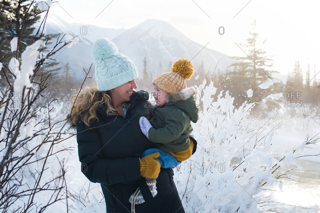 Mom holding toddler girl in snowy mountains