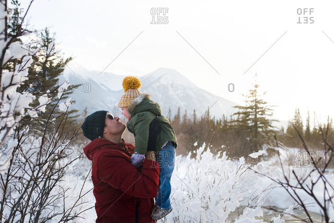 Dad holding up girl in snow mountains