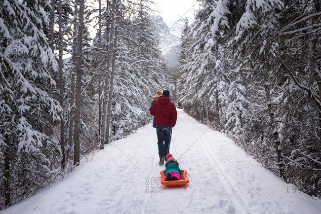 Dad pulling kids on snowy trail