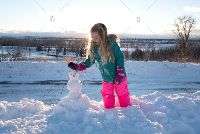Girl making a snowman in rural setting