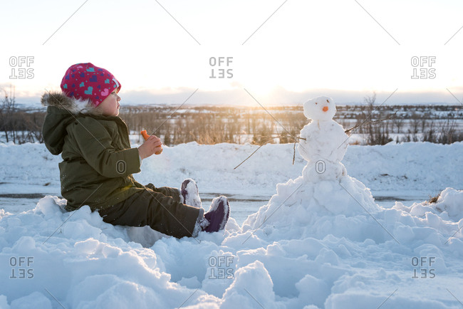 Girl eating carrot by snowman