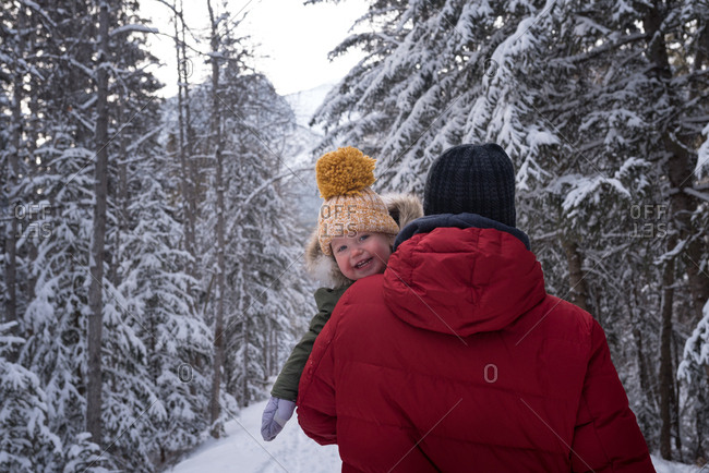 Dad carrying toddler on snowy trail