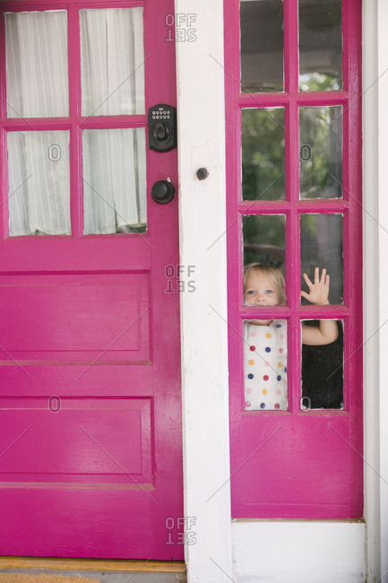 Girl peeking through door's window