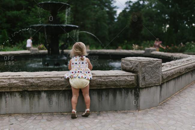 Toddler by fountain in garden