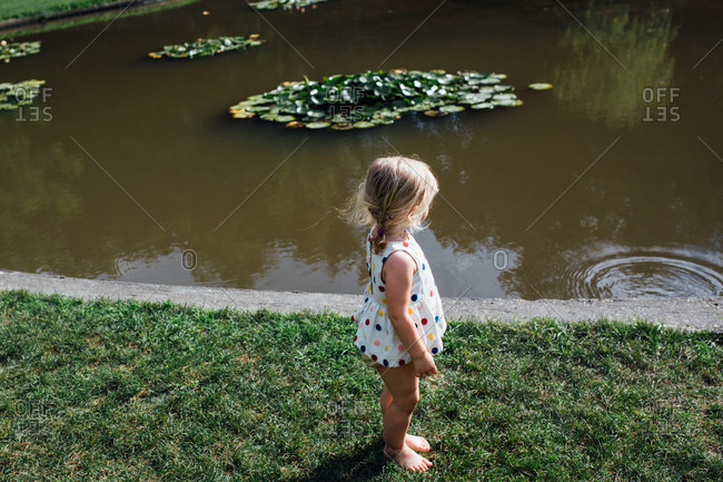 Toddler by pond with lily pads