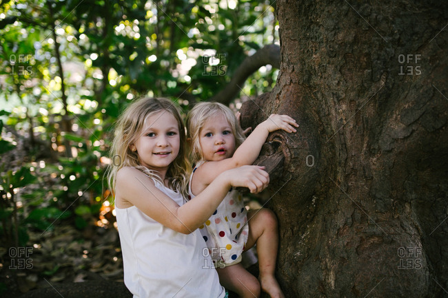 Girl with toddler balancing on tree