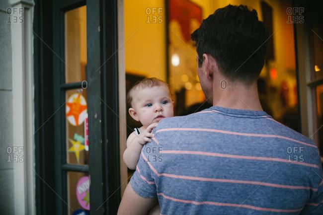 Man entering house carrying toddler