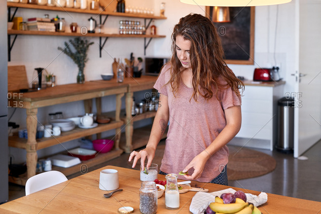 Healthy start to the day, woman at home preparing breakfast in a stylish kitchen