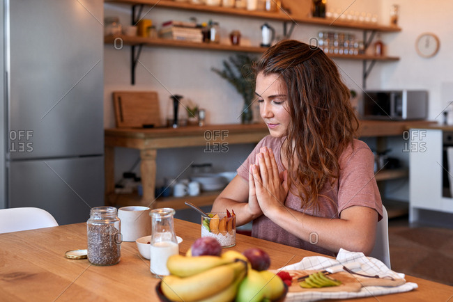 Spiritual woman giving thanks for the food before eating