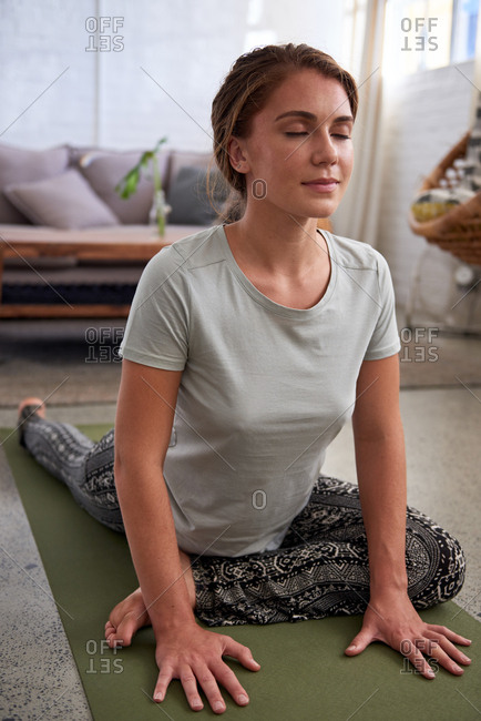 Healthy woman practicing yoga at home