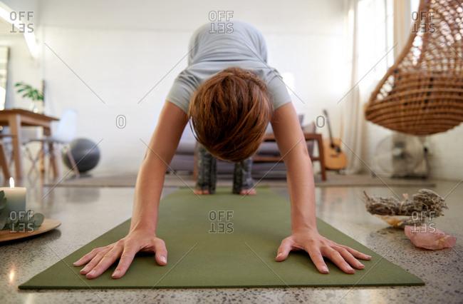 Woman doing yoga at home, surrounded by chakra balancing items
