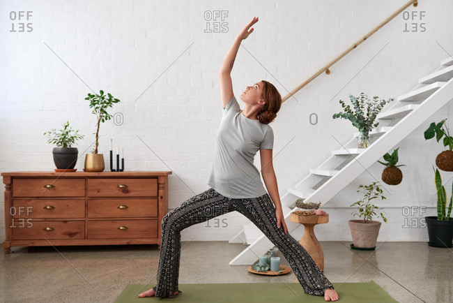 woman focusing on yoga flow sequence, reverse warrior pose