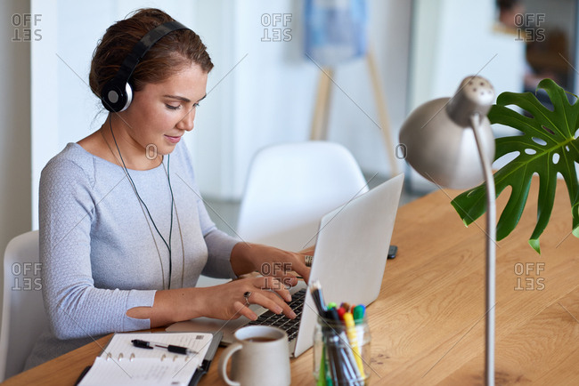 Independent woman focusing on work, listening to music while sending emails
