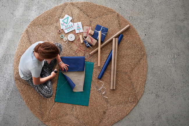Overhead view of woman wrapping Christmas gifts, preparing for the holidays