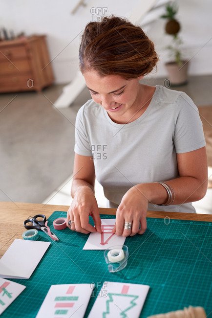 Young woman smiling while making handmade Christmas cards with washi tape
