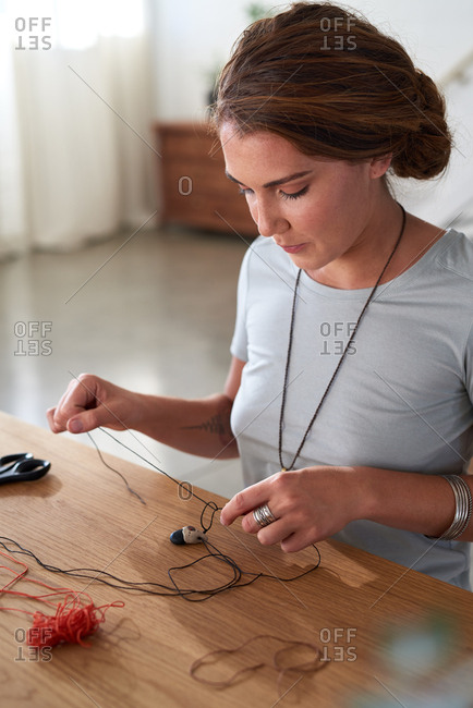 Artistic woman tying knots on her handmade necklace