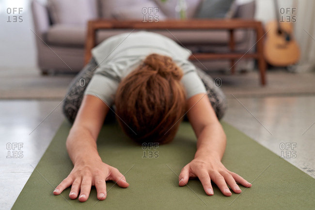 Woman practicing yoga at home, hands on mat child's pose