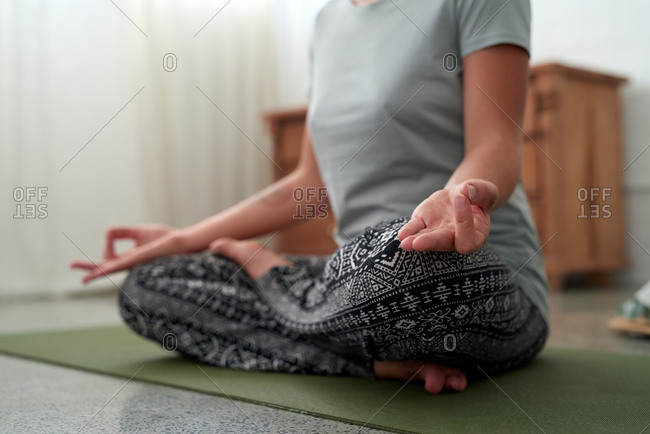 Woman practicing yoga at home, hands on knees meditating