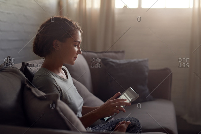 woman using technology at home in the evening