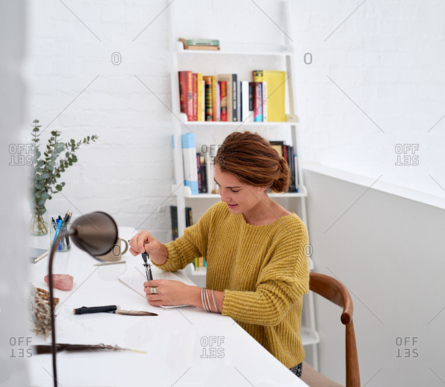 Woman in home office, drawing with compass