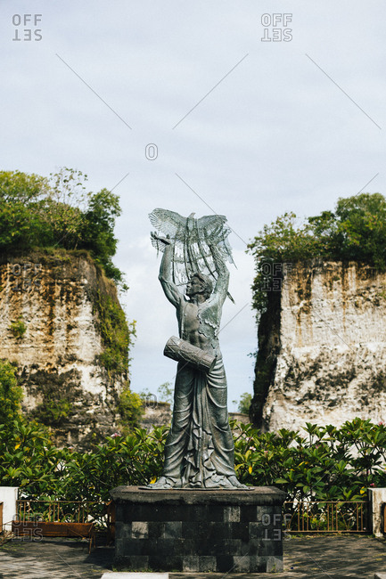 A large stone statue between two sheer cliffs at GWK Cultural Park in Bali, Indonesia.