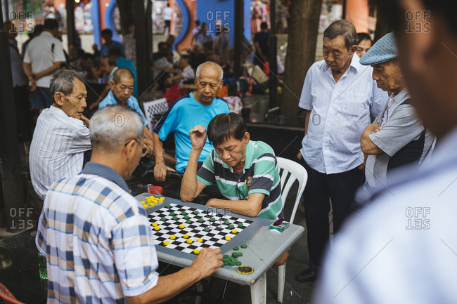 2/18/17: A group of men play chess near a hawker center in Chinatown, Singapore.
