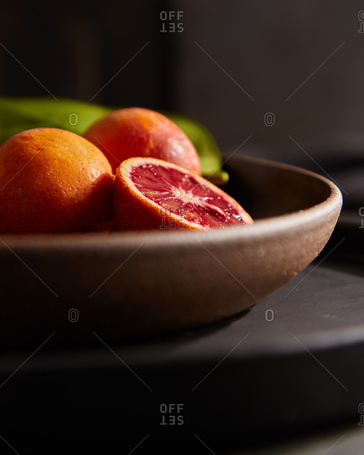 Close up of blood oranges in wooden bowl