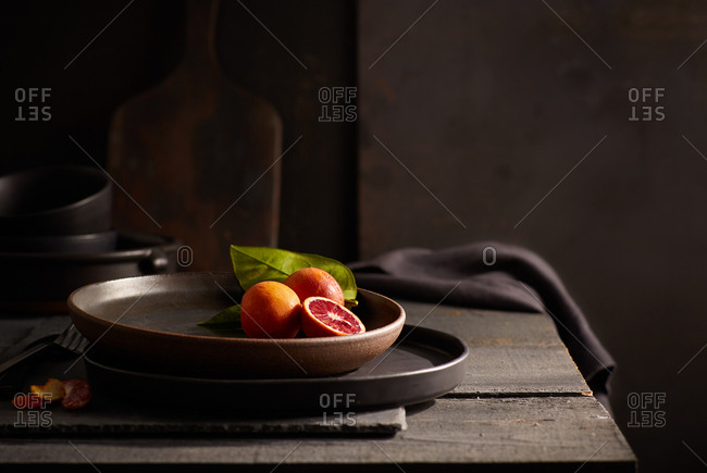 Still life of blood oranges in wooden bowl on table