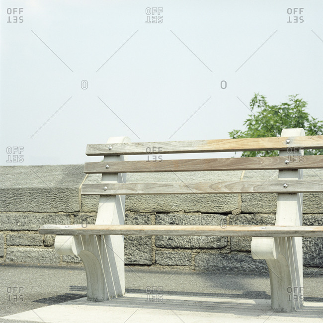 Empty park bench next to stone wall