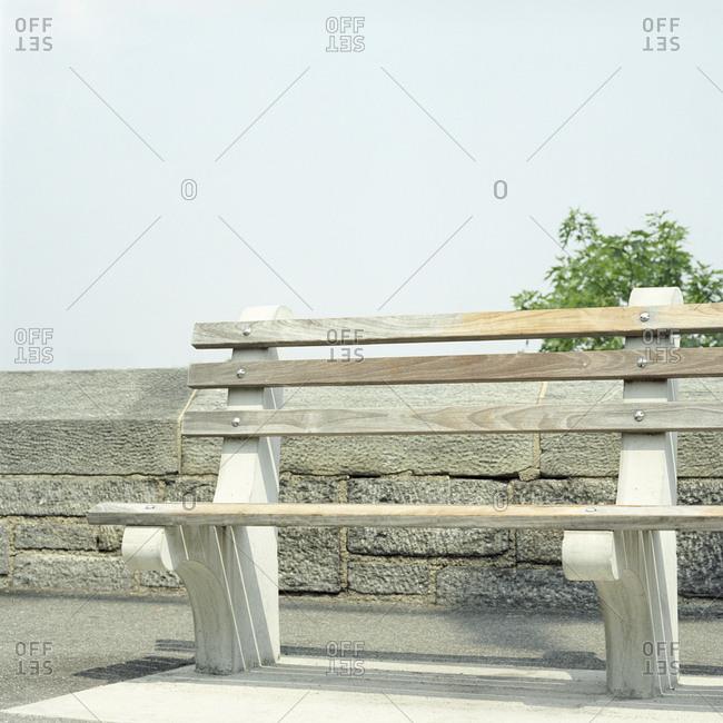 Empty park bench next to stone wall