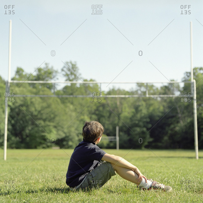 Boy sitting on field and looking at goal posts