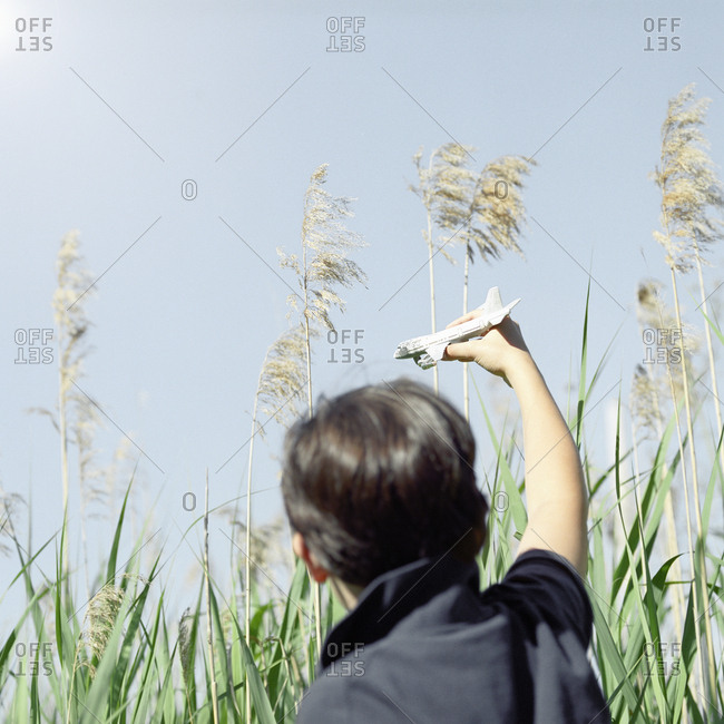 Boy playing with toy airplane in tall grass