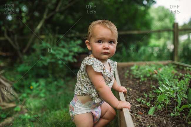 Cute baby girl standing next to raised garden bed