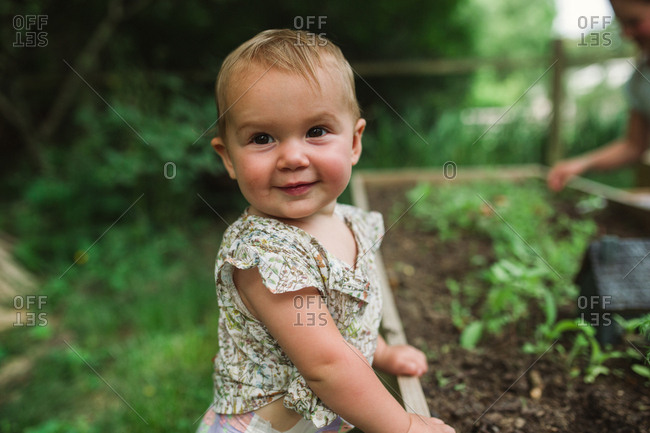 Close up portrait of a smiling baby girl standing next to a raised garden bed
