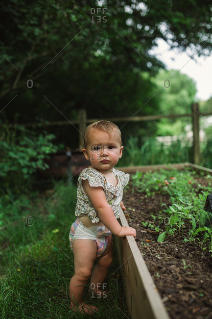 Portrait of a baby standing next to raised garden bed
