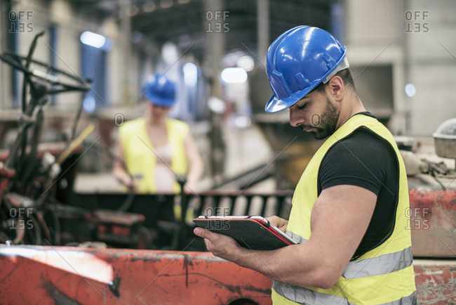 Portrait of worker with tablet and woman in background