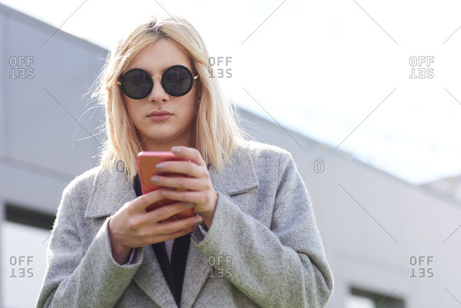 Portrait of fashionable transwoman. Low angle view of blond-haired  transgender in round sunglasses and stylish coat holding smartphone and texting message