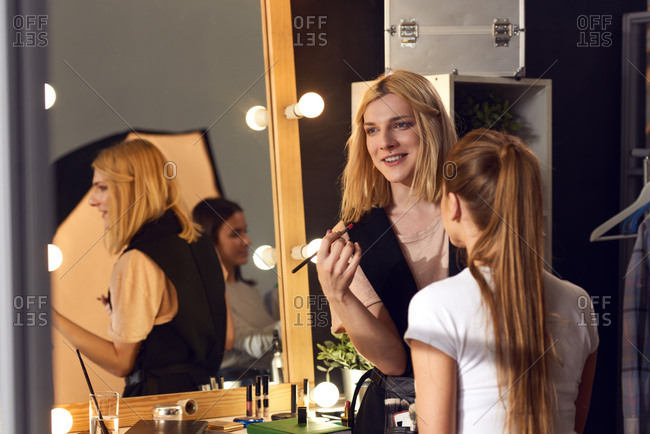 Transwoman in love with her profession. Young transgender make-up artist working with female model in studio and smiling cheerfully