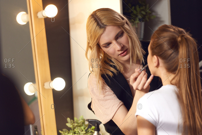 Transwoman in fashion business. Concentrated androgynous make-up artist applying make-up to female model in beauty salon