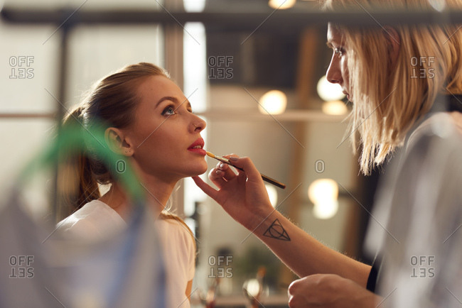 Professional transsexual make-up artist applying lipstick on lips of young attractive woman with nose piercing in beauty salon