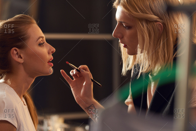 Profile view of concentrated transgender makeup artist putting lipstick with brush on young beautiful female model in studio